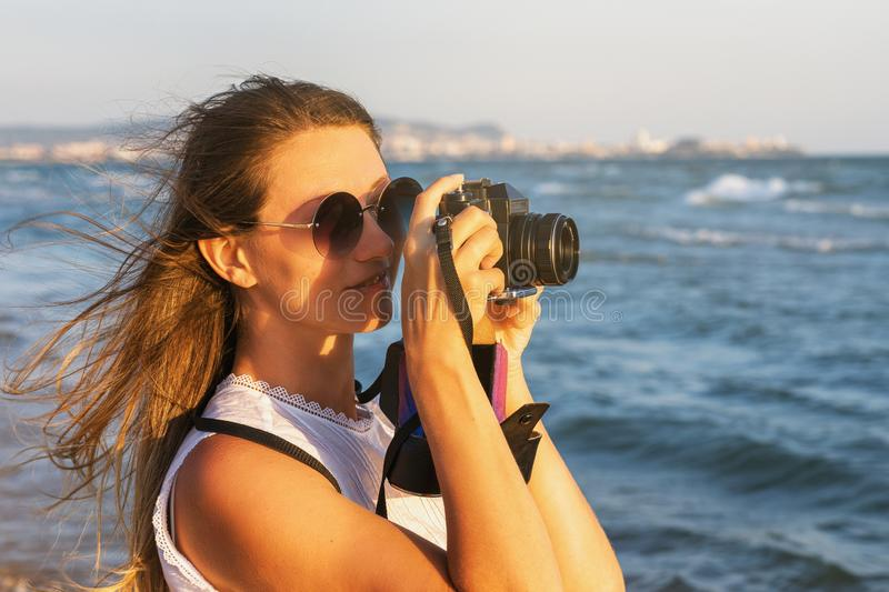 Girl tourist photographs the sights walking along the promenade near the sea stock image