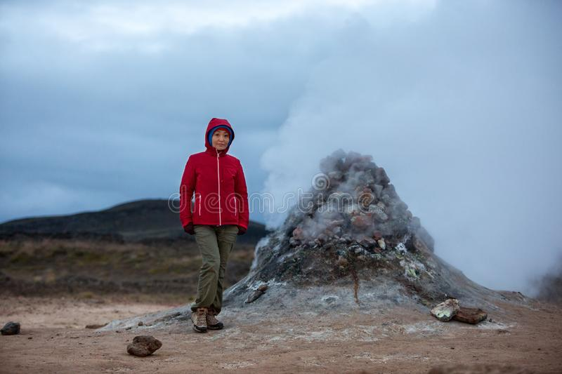 A girl tourist in a red jacket stands against the background of sulfuric smoke erupting from the ground royalty free stock image