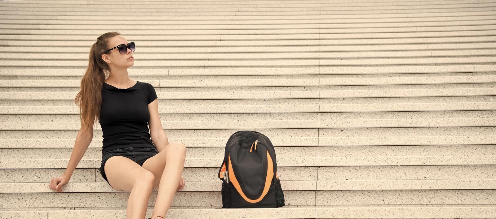 Girl tourist relaxing on stony stairs near her backpack. Take minute to relax. Woman sunglasses stylish black outfit stock photo