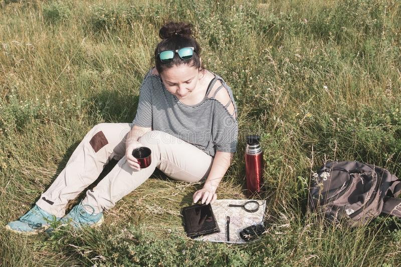 Girl tourist sitting in the grass, drinking tea from a thermos and making a route using a tablet and map. On the map are magnifier, binoculars, pen. Near the stock photos
