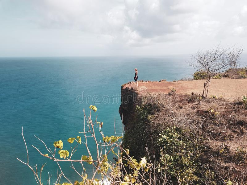 Girl tourist standing on the cliff stock photos
