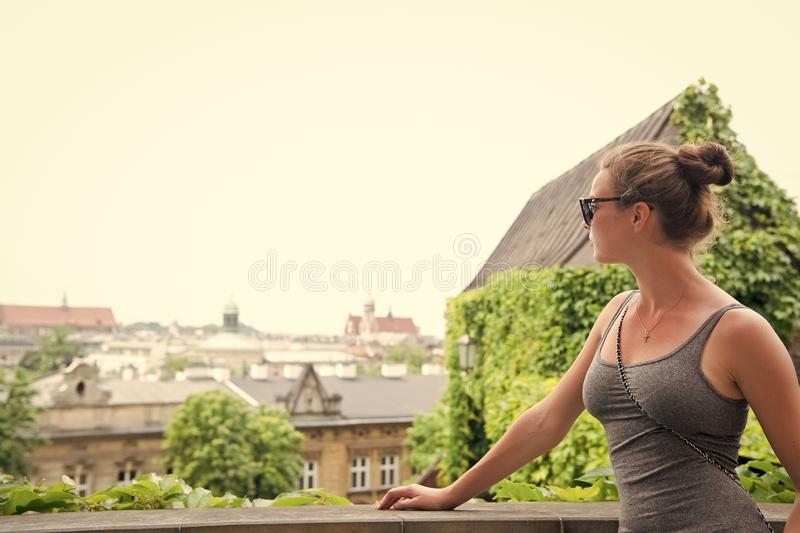 Girl tourist sunglasses enjoy view Krakow old city. Woman stand in front of architectural horizon with roofs and royalty free stock images