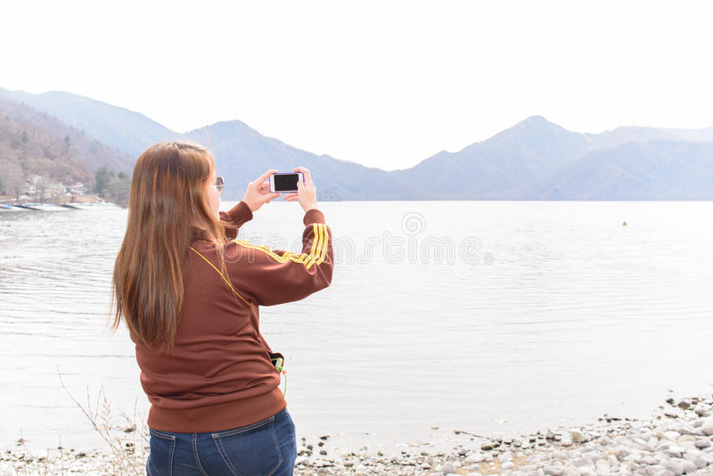 Girl tourist taking picture with mobile phone. Asian girl tourist taking travel picture with mobile phone stock photos