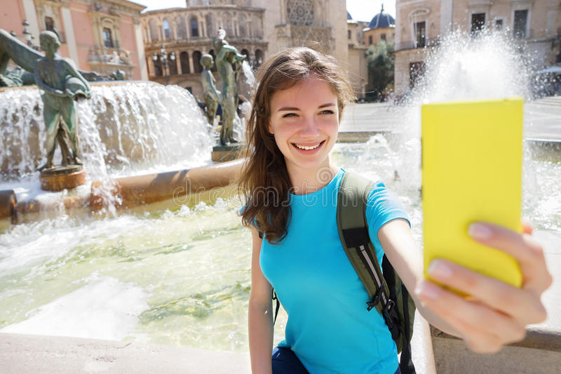 Girl tourist using smart phone camera to take photo while traveling in Valencia, Spain. royalty free stock images
