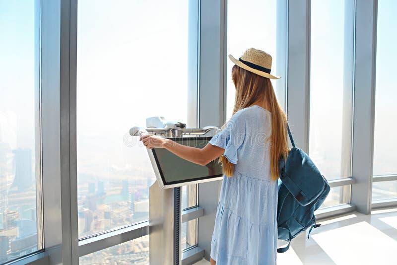 Girl tourist by the window of skyscraper of the Burj Khalifa in Dubai, United Arab Emirates stock photography