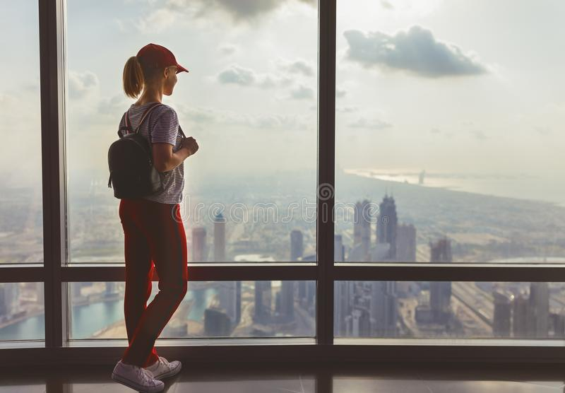 Girl tourist at window of skyscraper of the Burj Khalifa in Dubai, United Arab Emirates, UAE. January 2018 royalty free stock photography
