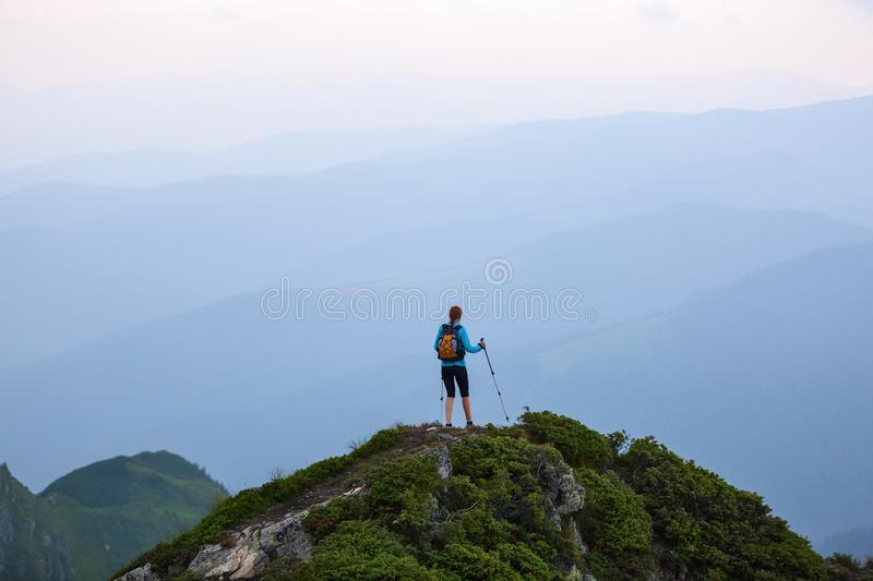 The girl with the touristic equipment goes up to the peak of the rocky high hill with the lawn. The scenery of the mountains. The girl with the touristic stock photos