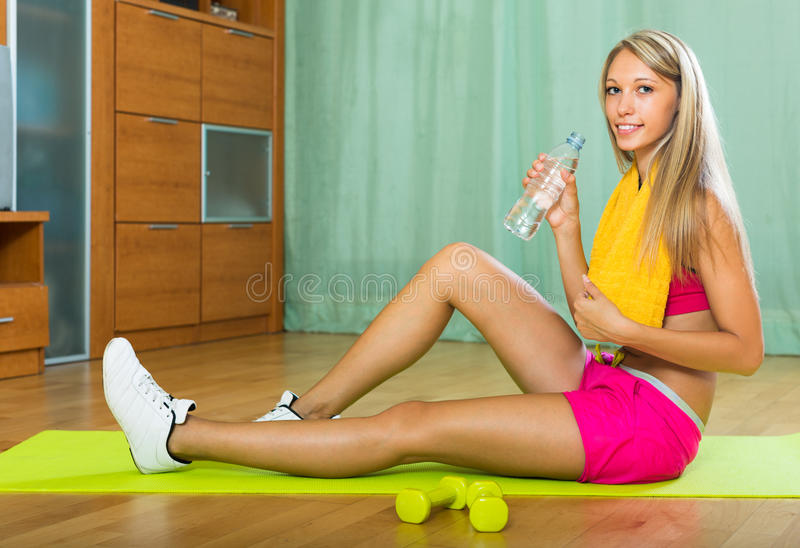 Girl with towel and bottle of water. Smiling sporty girl with bottle of water after exercising indoor stock images