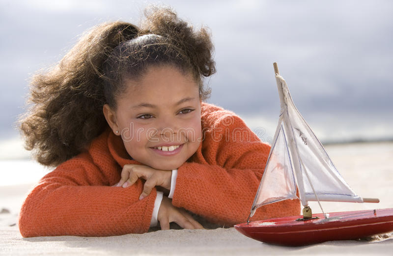 Girl (5-7) with toy boat on beach, smiling royalty free stock photography