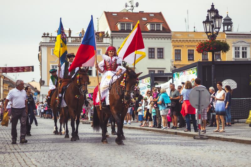 Girl in traditional costume with flag rides a horse stock photo