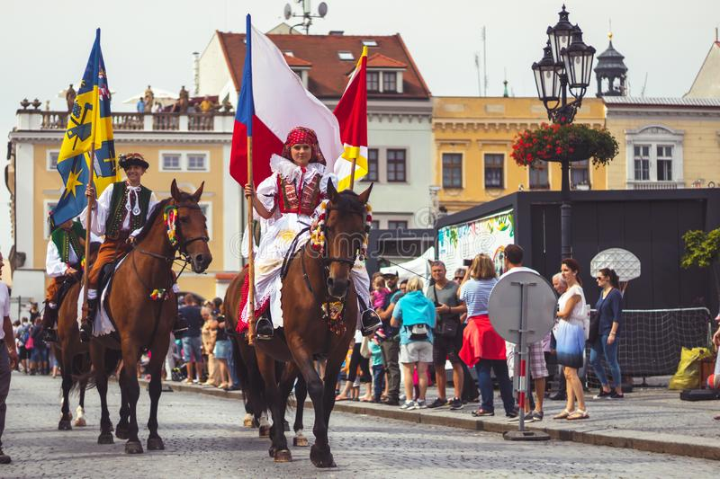 Girl in traditional costume with flag rides a horse stock image