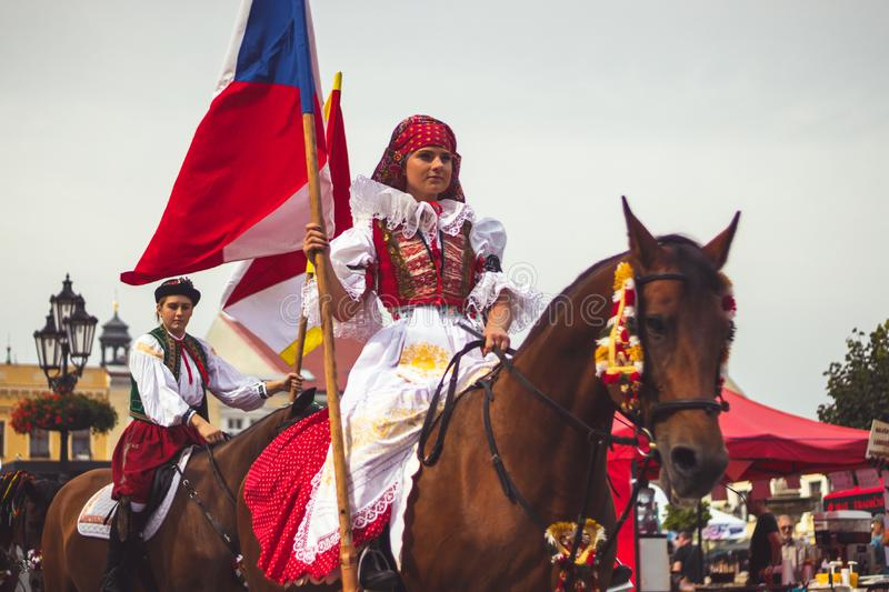 Girl in traditional costume with flag rides a horse stock photos