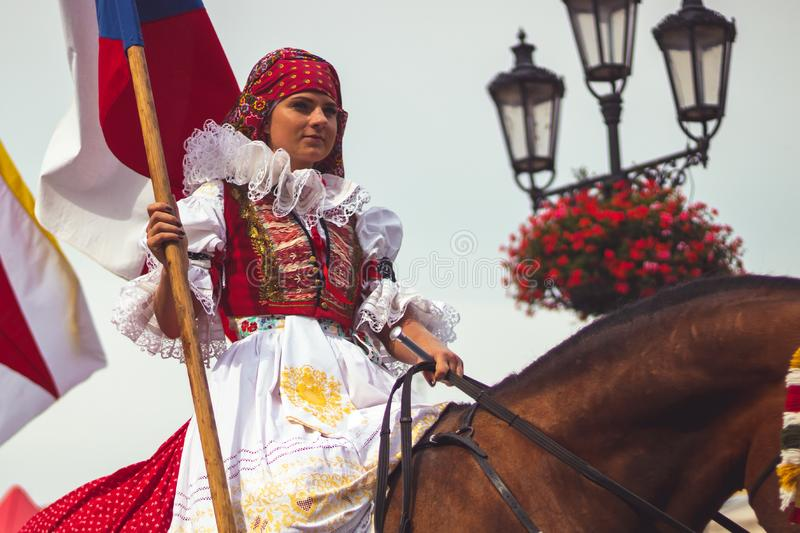 Girl in traditional costume with flag rides a horse stock photography