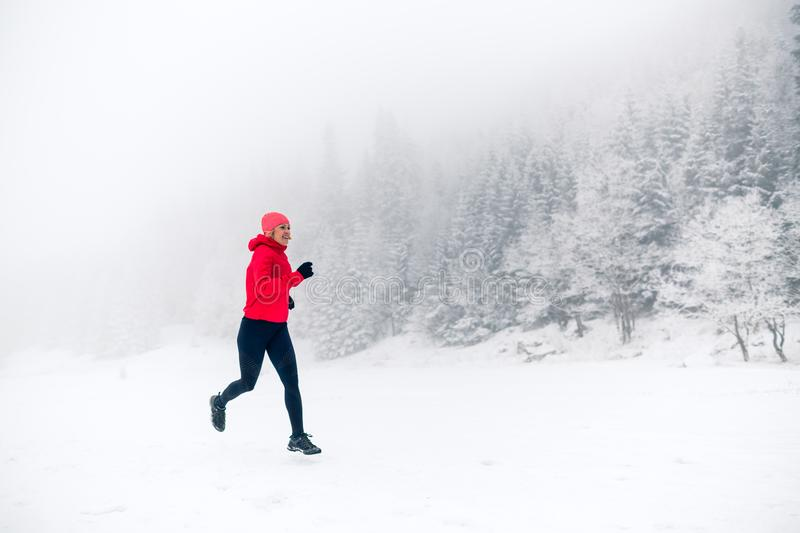 Girl trail running on snow in winter mountains royalty free stock image