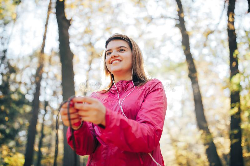 Girl train and listen to music in headphone. Jumping on a rope. Good morning light stock image