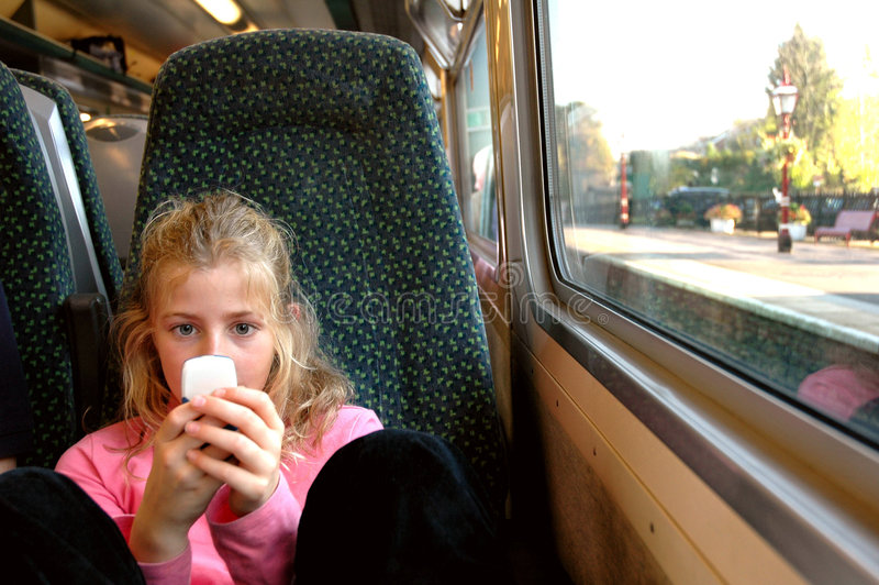 Girl on train with mobile phone. Nikon d70, candid portrait of child royalty free stock photography