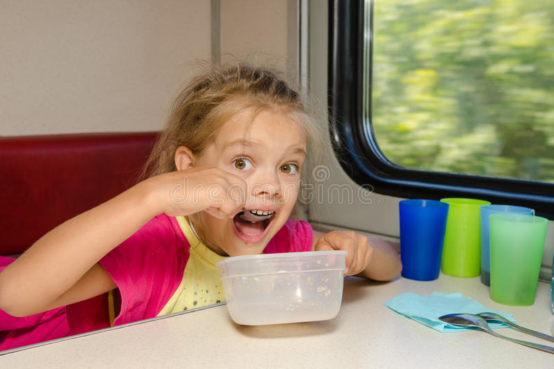 The girl on train sits at a table on the lower place in the second-class compartment of the car and eats it with relish spoon. The girl on the train sits at a royalty free stock images