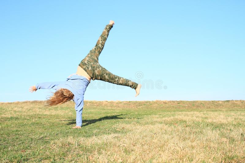 Girl training cartwheel. Exercising little kid - barefoot girl in khaki pants and blue jacket training cartwheel on green grass with blue sky behind. Childhood stock photography