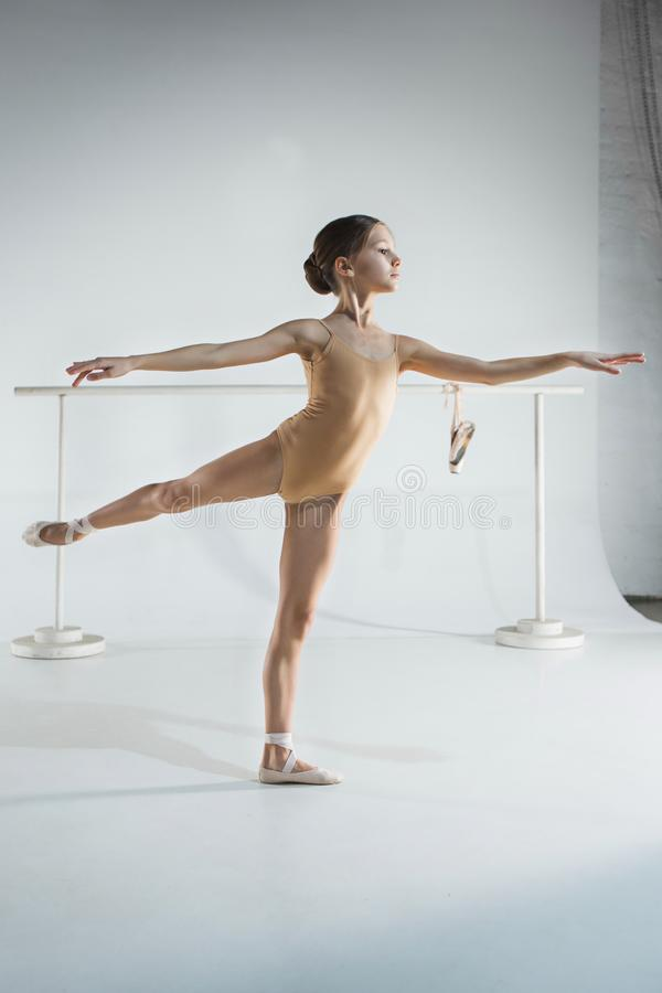 The girl is training near the ballet barre. stock image