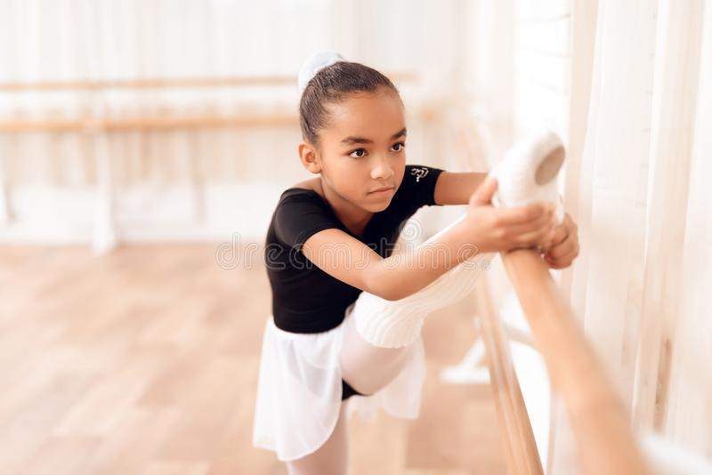 The girl is training a stretch of her legs near the ballet barr. stock image