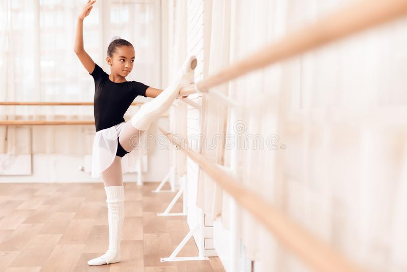 The girl is training a stretch of her legs near the ballet barr. stock images