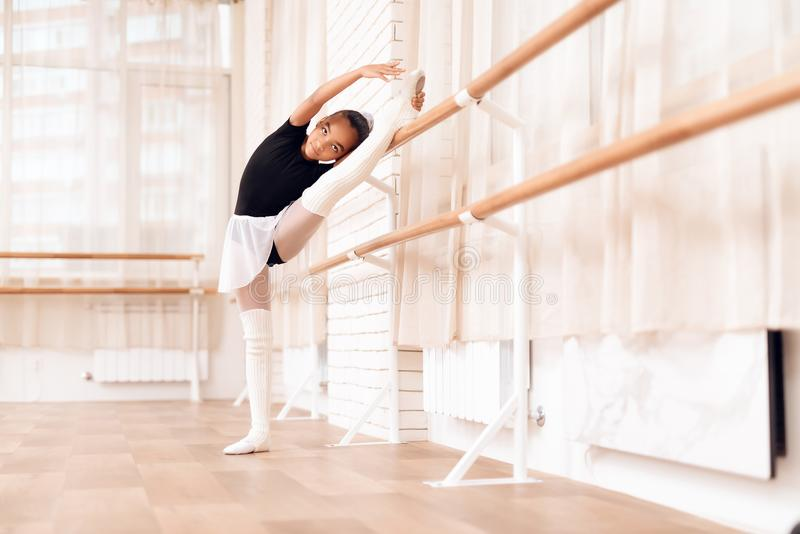 The girl is training a stretch of her legs near the ballet barr. royalty free stock photo