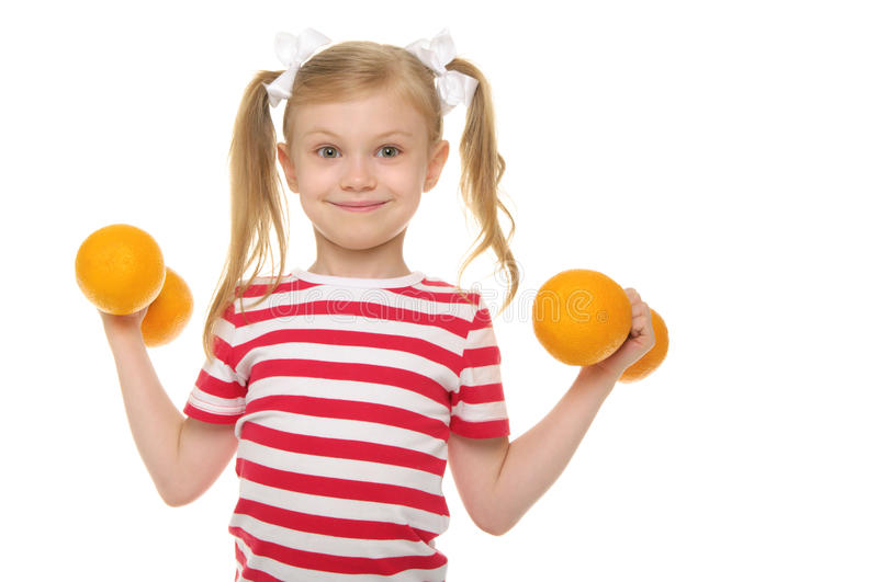 Girl trains fitness dumbbells of oranges stock photo