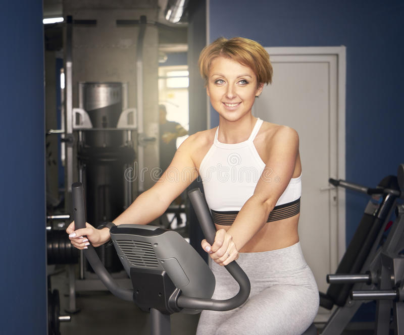 The girl trains in a gym on a bicycle stock photos