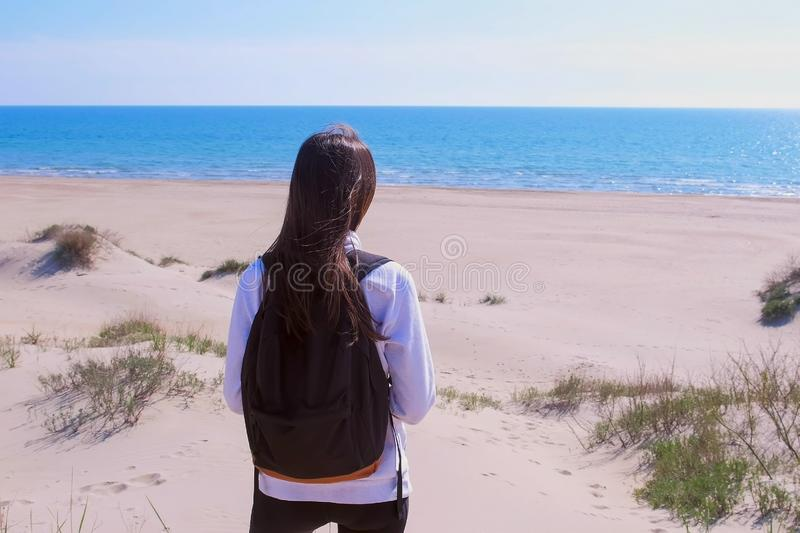 Girl travel stands on sand beach among dunes and look at sea vacation back view. Girl traveller with backpack on sea vacation. She is standing on the sea sand stock image
