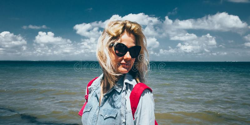 Girl traveler with a backpack stands on the background of the sea and enjoys the beautiful scenery. Concept of travel, adventure, stock photo