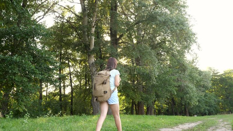 Girl traveler with a backpack walks along a forest road. Hiker woman walks in the forest. happy hiker girl in summer royalty free stock photo