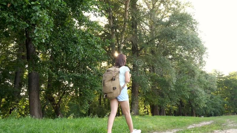Girl traveler with a backpack walks along a forest road. Hiker woman walks in the forest. happy hiker girl in summer royalty free stock photography