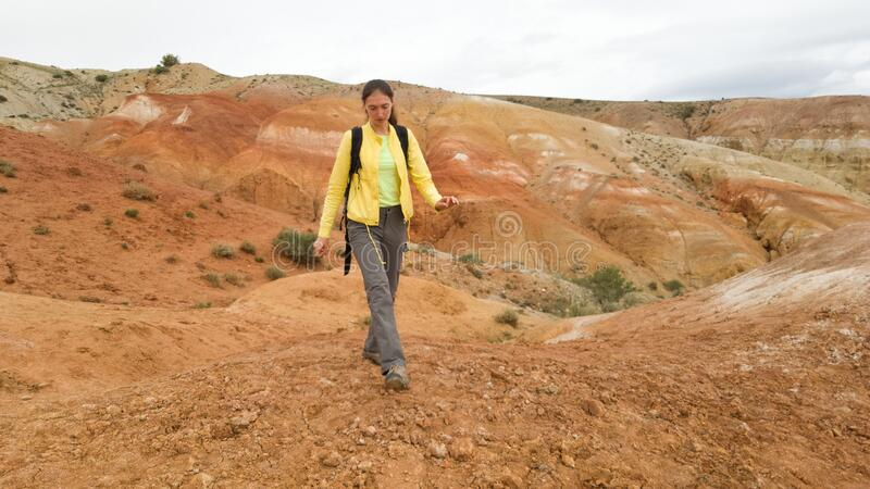 A girl traveler in a bright yellow jacket walks on the Altai Mars-the Kyzyl-Chin mountains in the Altai Republic in Russia. Summer royalty free stock photography