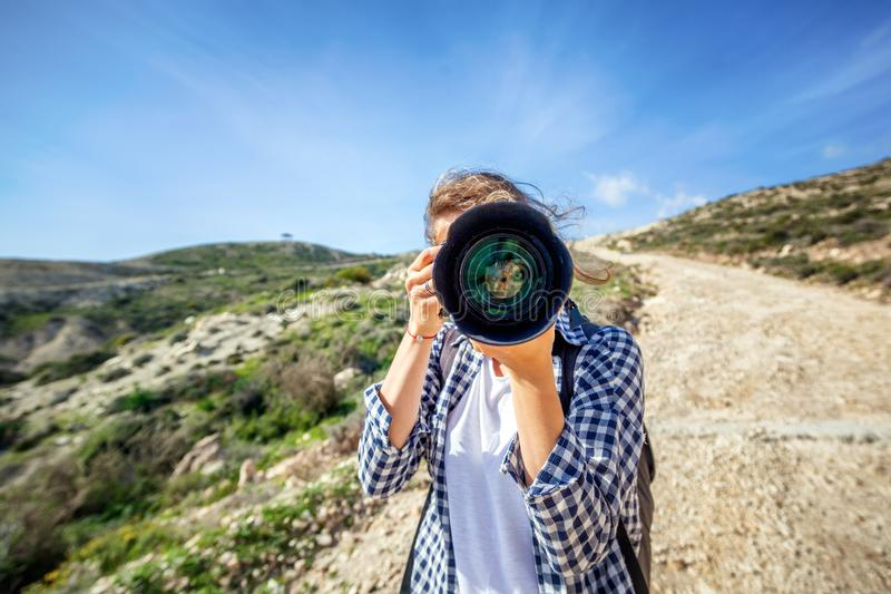 Girl traveler with a camera in hand, against a beautiful summer stock image