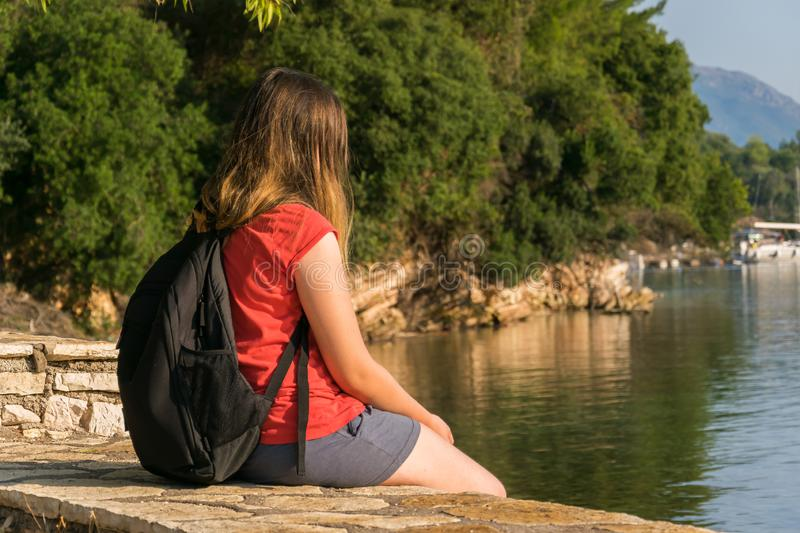 Girl traveler, enjoys the view of the sea, rocks, conifers.  royalty free stock images