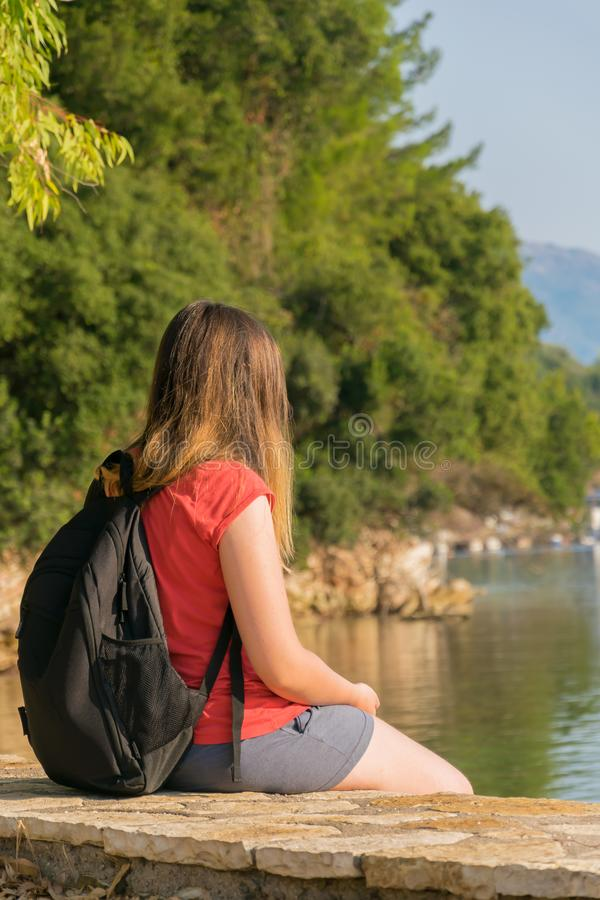 Girl traveler, enjoys the view of the sea, rocks, conifers.  stock photo