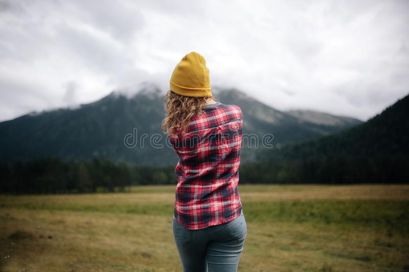 Girl traveler in hat with backpack looking at clouds in mountains stock images