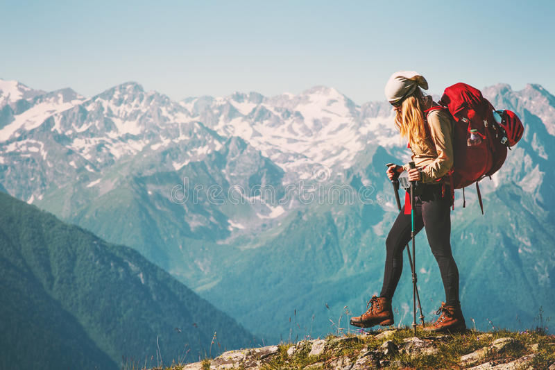 Girl Traveler hiking with backpack at rocky mountains royalty free stock image