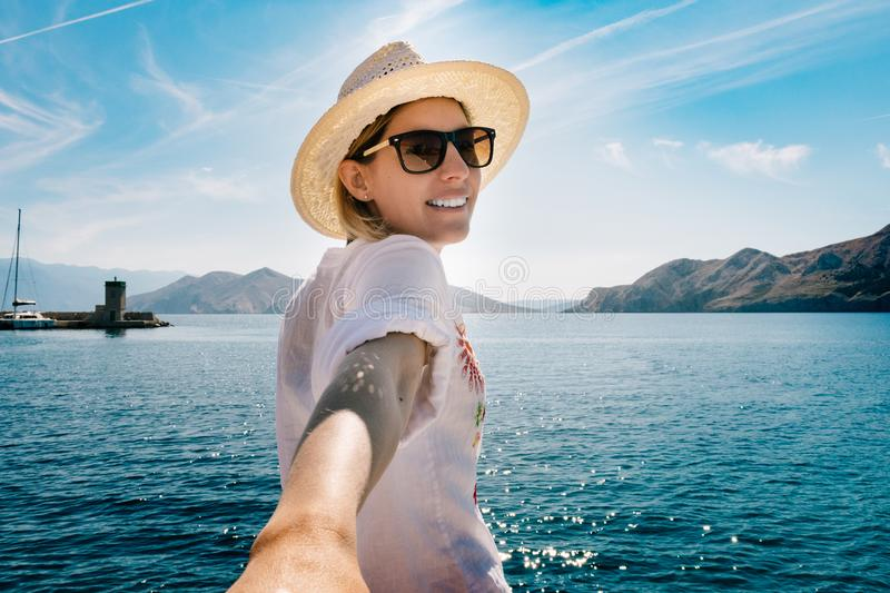 Girl traveler keeps your boyfriend on the holiday by the sea. Follow me on vacation. Happy vacation memories royalty free stock photos