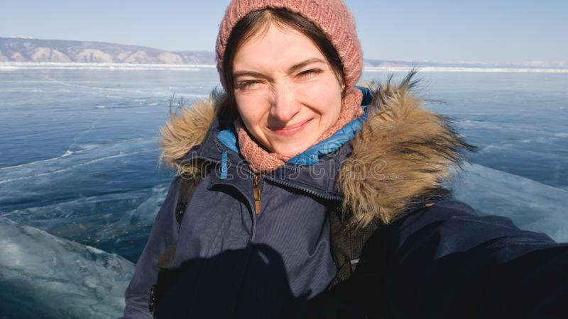 Girl traveler makes a selfie on the winter lake Baikal. The lake in the ice. The sun is bright, the girl wrinkles her nose stock photography