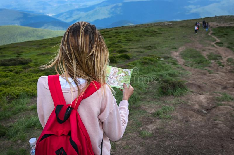 Girl traveler with a red backpack, she lost in the mountains, in the woods looks at the map royalty free stock images