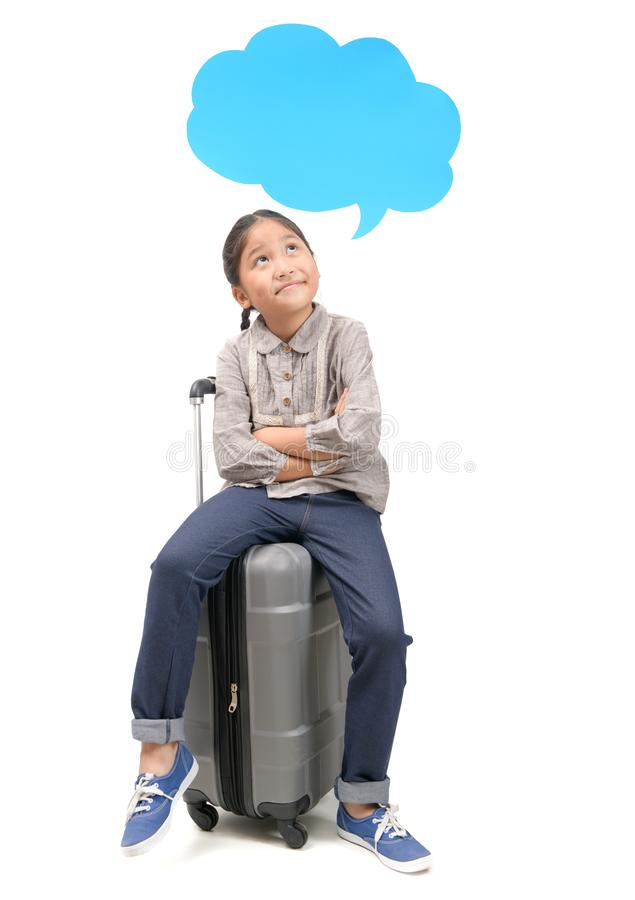 Girl traveler sit on suitcase and thinking with speech bubble stock photo