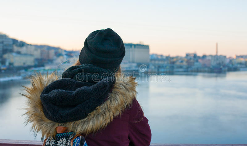 Girl traveler standing on the bridge enjoying view of the city stock photos