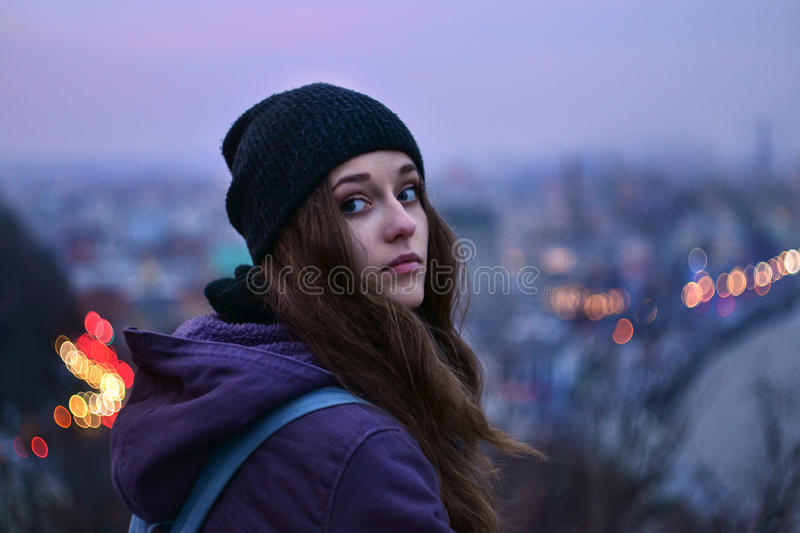 Girl traveler standing in front of winter evening cityscape. Hipster girl traveler in hat standing in front of winter evening cityscape, purple sky and blurred royalty free stock photo