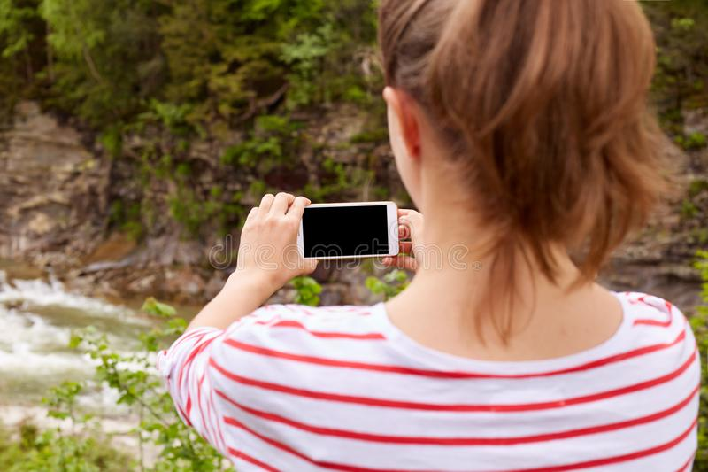 Girl traveler takes photo of lush mountain river in ravine on smartphone, selective focus, enjoing natures landscapes, female royalty free stock photos