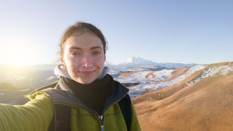 A girl traveler takes a selfie on the background of mount Elbrus. Warm coat. Autumn trip to Russia. The glare of the sun. Bright stock image