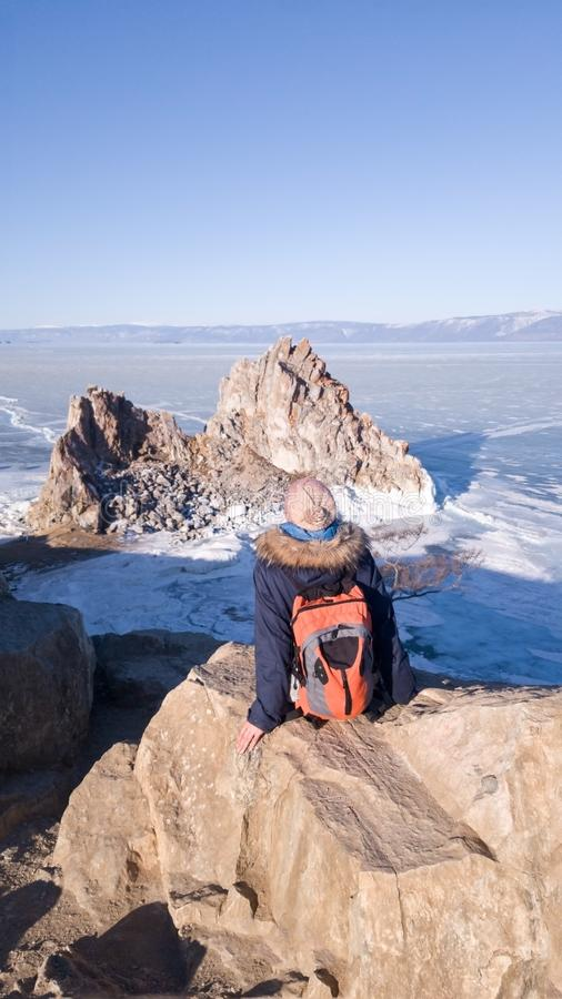Girl traveler in warm clothes in winter sitting on Cape Burhan and admires the rock Shaman on the island of Olkhon on lake Baikal. stock photos
