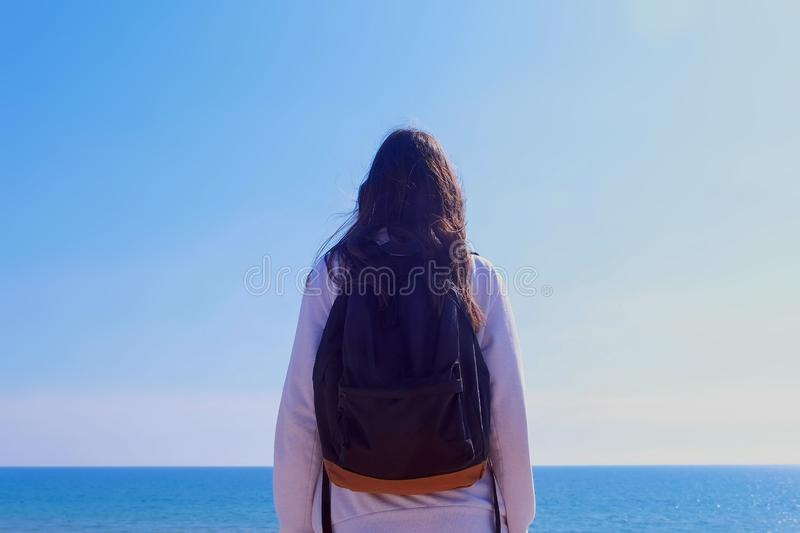 Girl traveller with backpack stands looks at sea on vacation side view outdoor. Girl brunette traveller with backpack is looking at sea standing on center, back stock images