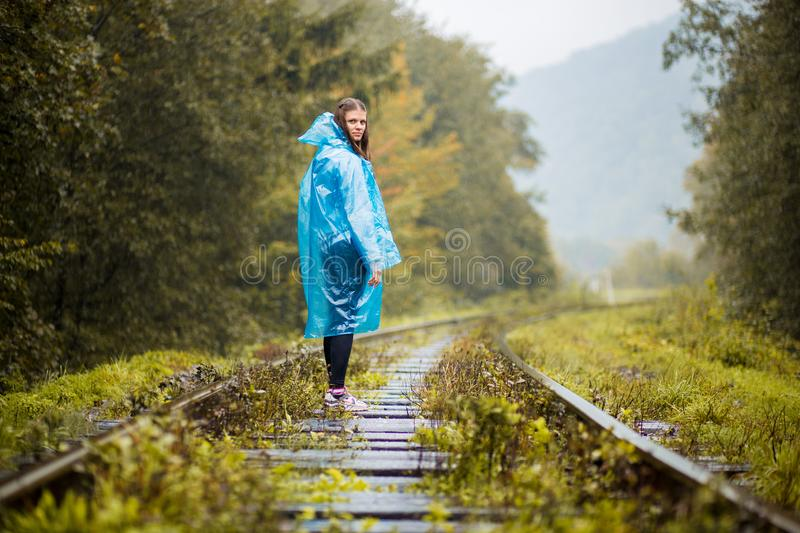 Girl traveller wearing blue jacket and go by forest railway. Autumn and raining season royalty free stock image