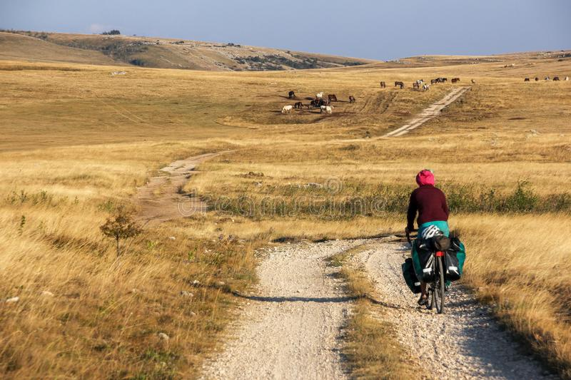 Girl travels on bycicle on gravel road. stock images